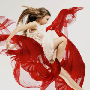 young female dancer in a white dress enveloped by a red sheer scarf swirling around here
