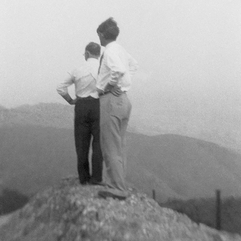 black and white photo of two men standing on a dirt mound