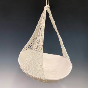 ceramic bowl hanging precariously in a partial net
